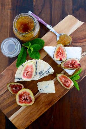 tabla de quesos: Higos frescos en corte de madera tabla de cortar con el tarro de jalea de higo preservar y queso gourmet en madera oscura mesa rústica de fondo, vista aérea.