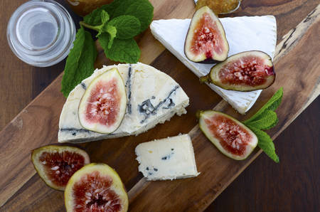 cheeseboard: Fresh figs on wooden cutting chopping board with jar of fig jelly preserve and gourmet cheese on dark wood rustic table background, overhead view.