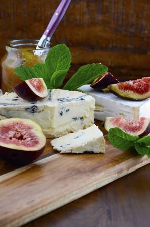 cheeseboard: Fresh figs on wooden cutting chopping board with jar of fig jelly preserve and gourmet cheese on dark wood rustic table background, with copy space.