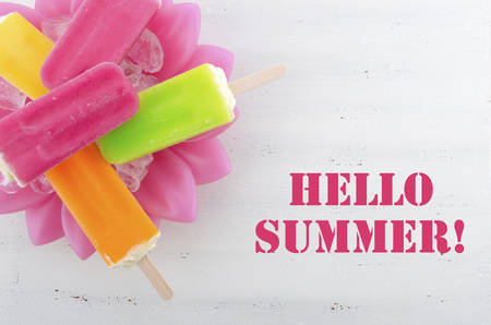 july: Summer is Here concept with bright color ice pop, ice creams with Hello Summer text. Stock Photo