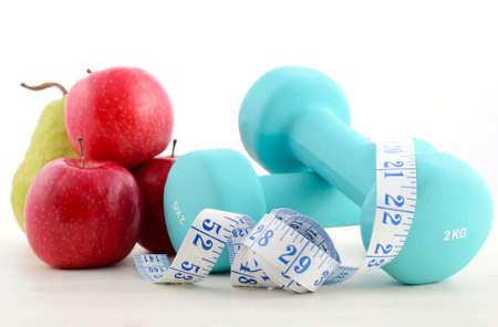 SALUD: Salud y concepto de fitness con pesas azul, cinta métrica y fruta fresca en el blanco apenado fondo de la tabla de madera.