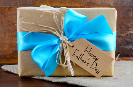 christmas gift tag: Happy Fathers Day natural kraft paper wrapped gift owith pale blue ribbon on dark wood background.