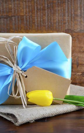 azul turqueza: Día de padres feliz, o el cumpleaños masculino, papel kraft natural, envuelto regalo con la cinta azul claro en el fondo de madera oscura.