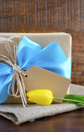 blue gift box: Happy Fathers Day, or masculine birthday, natural kraft paper wrapped gift with pale blue ribbon on dark wood background.
