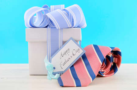 Happy Fathers Day Gift with Blue and White Ribbon with red and blue stripe neck tie and gift tag on white wood table and pale aqua blue background.