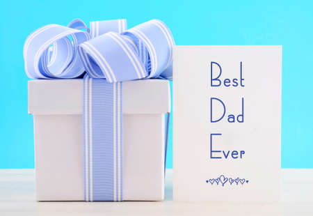 aqua background: Happy Fathers Day Gift with Blue and White Ribbon with Best Dad Ever greeting card on white wood table and pale aqua blue background.