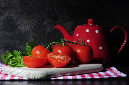 kitchen bench: Dramatic red vintage style kitchen still life with tomatos, chopping board, polka dot tea pot on red check napkin against a black slate kitchen bench top. Stock Photo