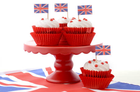 Red white and blue theme cupcakes on red cake stand with UK Union Jack flags on white wood table for Queens Birthday and Great Britain party food.