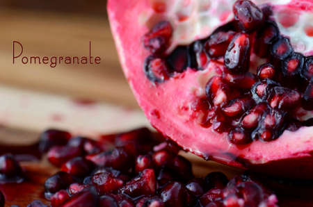 Reclaimed: Close up of seeds of pomegranate fruit on vintage wood background with text.