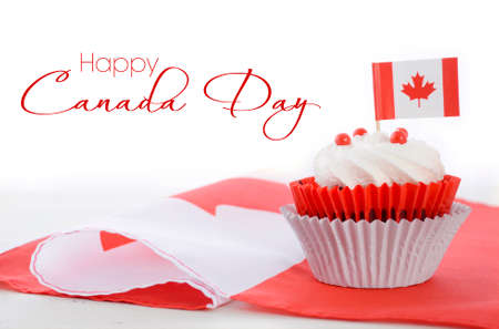 幸せなカナダデーのお祝いケーキ白の木製テーブルとサンプル テキストの赤と白のカナダのメープル リーフ フラグ。 写真素材