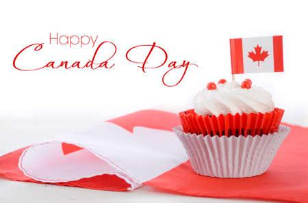 Gelukkig Canada Day viering cupcake met rode en witte Canadese esdoornblad vlag op witte houten tafel, en voorbeeld tekst.