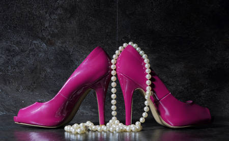 country side: Glamorous pair of ladies pink high heels with long strand of white pears against a dramatic black slate background still life.
