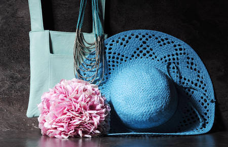 pink hat: Ladies vintage retro style apparel with aqua blue sun hat, shoulder bag and necklace with bunch of pink hydrangea flowers against a dramatic black slate background.