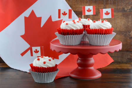 Happy Canada Day celebration cupcakes on red cake stand with red and white maple leaf flag against a rustic distressed wood background. Stock Photo
