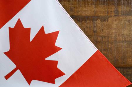 Canadese rode en witte vlag van het esdoornblad tegen een donkere houten rustieke achtergrond voor de Dag van Canada, 1 juli viering en nationale feestdagen.