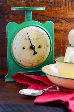 reclaimed: Vintage kitchen scales and tin cups and pans on dark reclaimed wood background. Stock Photo
