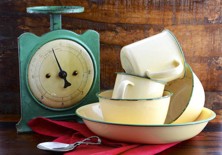 vintage kitchen: Vintage kitchen scales and tin cups and pans on dark reclaimed wood background. Stock Photo