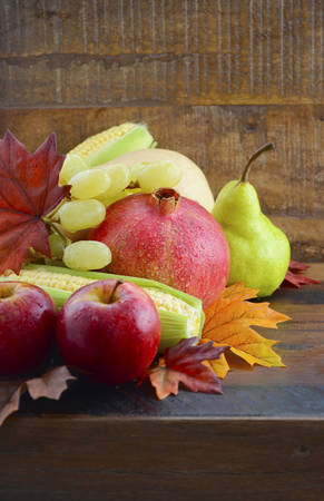 Autumn Fruit and Vegetable Background with fresh butternut pumpkin, grapes, leaves, apples, pear, pomegranate, and corn, with copy space for your text here.. photo