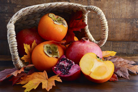 pomegranate: Basket of fresh persimmons and pomegranates with cut slices on Autumn Fall leaves against a dark wood vintage background. Stock Photo