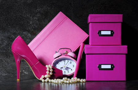 Ladies pretty pink female office desk with high heel shoe, clock, pen, stationery filing boses, pearls and diary organiser against a dramatic black background.