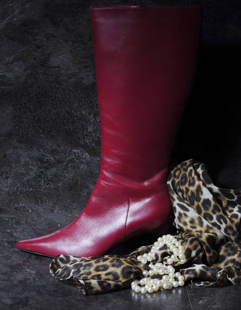 clasp feet: Tall ladies red high hells boots with animal print scarf and pearl necklace against a dramatic black slate background still life.