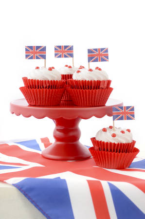queen's birthday: Red white and blue theme cupcakes on red cake stand with UK Union Jack flags on white wood table for Queens Birthday and Great Britain party food. Stock Photo