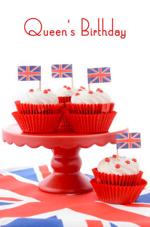 queen's birthday: Red white and blue theme cupcakes on red cake stand with UK Union Jack flags on white wood table with Queens Birthday sample text. Stock Photo