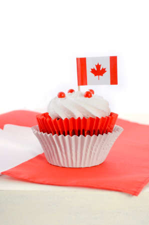canadian maple leaf: Happy Canada Day celebration cupcake with red and white Canadian maple leaf flag on white wood table.