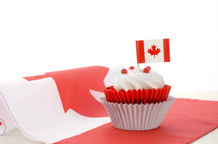 canada day: Happy Canada Day celebration cupcake with red and white Canadian maple leaf flag on white wood table.