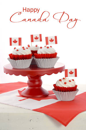 canada day: Happy Canada Day celebration cupcakes with red and white maple leaf flag on red cake stand against a white background, vertical with sample text.