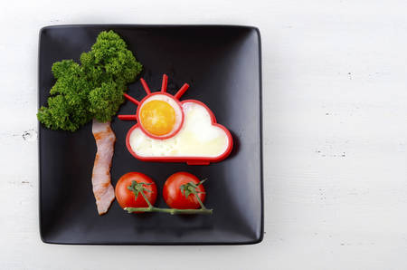 sunnyside: Bright happy breakfast with sunny egg, bacon tree with parsley leaves and cherry tomato flowers on black square plate on white wood table.