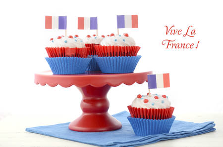 bastille: Red, white and blue theme cupcakes on white wood table for Bastille Day or French party celebration.