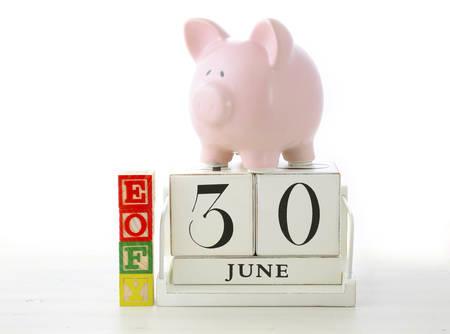 Einde van het boekjaar besparingen Concept met spaarvarken, EOFY bouwblokken en houten kalender op een witte houten tafel.