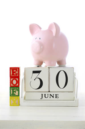 the end of the year: End of Financial Year Savings Concept with piggy bank, EOFY  building blocks and wood calendar on white wood table. Stock Photo