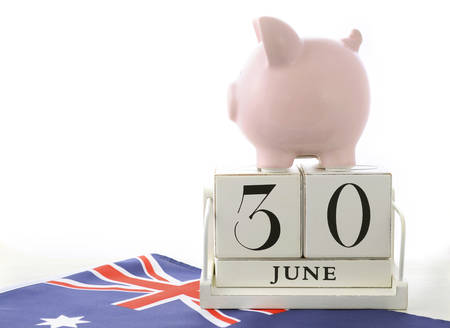 downunder: End of Financial Year Savings Concept with piggy bank and wood calendar and Australian Flag on white wood table.