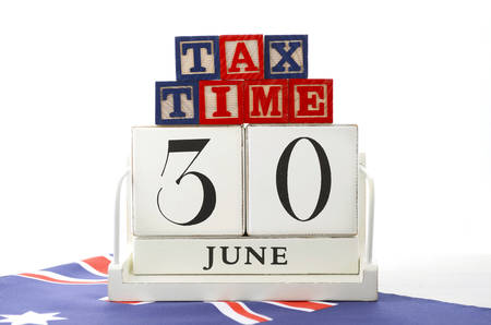 end of year: End of Financial Year Savings Concept with tax time building blocks and wood calendar and Australian Flag on white wood table.