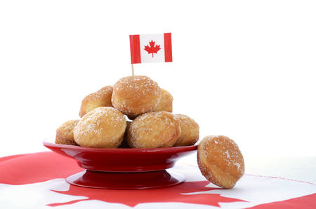 canadian maple leaf: Stack of donut holes on red plate on Canadian maple leaf flag for Happy Canada Day celebration party. Stock Photo