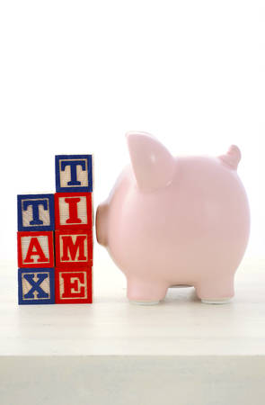 end of year: End of Financial Year Savings Concept with piggy bank, building blocks with tax time on white wood table.