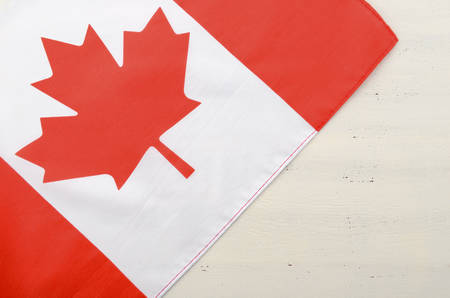 red maple leaf: Canadian red maple leaf flag on white wood shabby chic table with copy space for your text here.