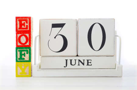 financial: End of Financial Year Savings Concept with end of financial year building blocks and wood calendar on white wood table.