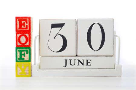 fin de ao: Fin de A�o Concepto Ahorro financiero con fines de bloques de construcci�n a�o financiera y el calendario de madera en la mesa de madera blanca. Foto de archivo