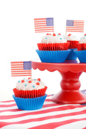 independance: Happy Fourth of July Cupcakes on red stand with USA flags on white wood shabby chice table. Stock Photo