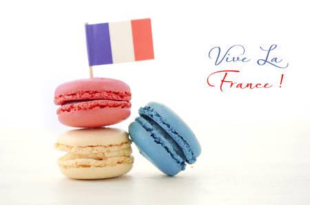 pasteleria francesa: Feliz rojo Día de la Bastilla, macarons blanco y azul con la bandera francesa en la mesa de madera blanca con Vive La France texto de ejemplo.