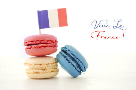bastille: Happy Bastille Day red, white and blue macarons with French flag on white wood table with Vive La France sample text.