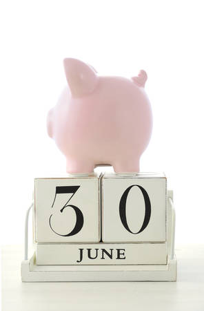 downunder: End of Financial Year Savings Concept with piggy bank and wood calendar on white wood table.
