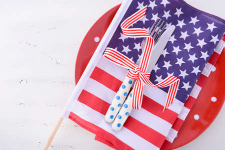 independance: Patriotic table place setting with USA flag and polka dot plate on white wood shabby chic table for Fourth of July and USA holiday and events celebration. Stock Photo