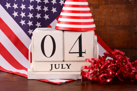 Vierde juli vintage houten kalender met vlag en feest hoed en decoraties op de rustieke achtergrond van donker hout.