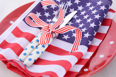 july 4th: Patriotic table place setting with USA flag and polka dot plate on white wood shabby chic table for Fourth of July and USA holiday and events celebration. Stock Photo