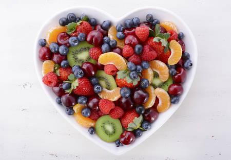다채로운 무지개 열매는 라스베리, 딸기, 체리, 블루 베리, manadrines 및 흰색 초라한 세련 된 고민 된 테이블, 오버 헤드보기 심장 모양 그릇에 키 위 과