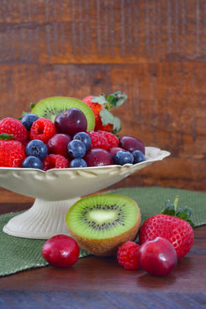 reclaimed: Summer Fruit including raspberries, strawberries, cherries, blueberries and kiwi fruit in a vintage bowl with reclaimed dark wood background. Stock Photo